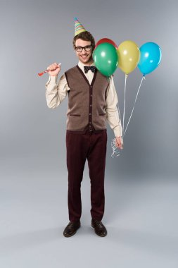 happy man in glasses and party cap holding multicolored balloons and party horn on grey background