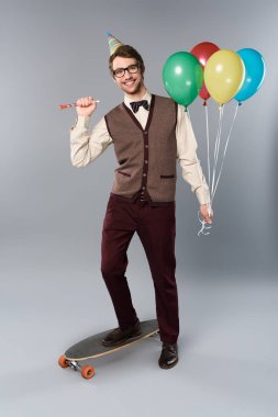 happy man in glasses and party cap holding multicolored balloons and party horn while standing on longboard on grey background