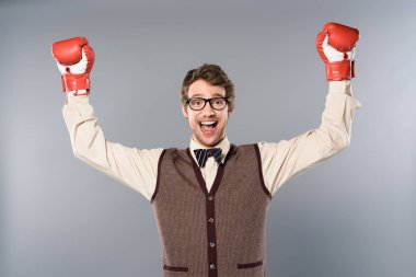 happy man in glasses and boxing gloves rejoicing on grey background