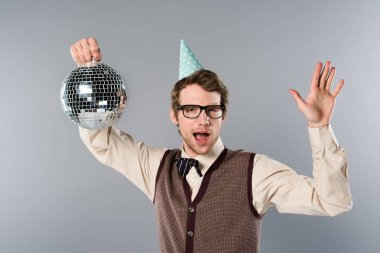 excited man in party cap with open mouth holding shiny disco ball and dancing