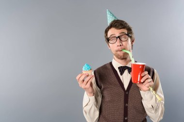 man in glasses and party cap with funny face expression holding cupcake and drinking soda