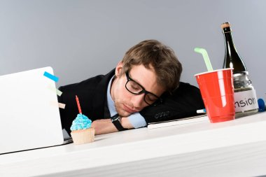 businessman sleeping at workplace near cupcake and paper cup isolated on grey