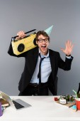 Fotografie happy businessman at workplace in party cap with vintage tape recorder on grey background