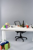 messy workplace with champagne bottle, paper cups, pension moneybox and laptop on white table near gift boxes