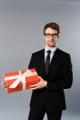 smiling businessman holding present with ribbon on grey background