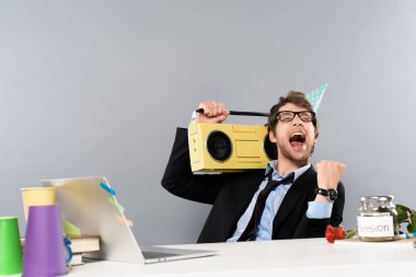 happy businessman sitting at workplace in party cap with vintage tape recorder and rejoicing on grey background
