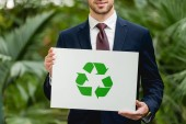 cropped view of smiling businessman in suit holding card with green recycling sign in greenhouse