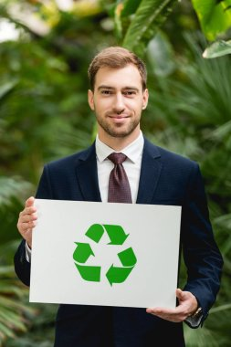 Handsome smiling businessman in suit holding card with green recycling sign in greenhouse stock vector