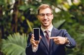 mosolygó üzletember öltöny, nyakkendő és szemüveg mutat ujjal az üres okostelefon képernyő az üvegházhatást okozó