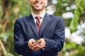 vista parziale di uomo daffari sorridente in giacca e cravatta tenendo germoglio verde e terra in mano in arancione