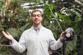 Lächelnder, gut aussehender Wissenschaftler in weißem Mantel und Brille mit geschlossenen Augen, der eine Gummigasmaske in der Orangerie hält