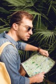 handsome tourist in sunglasses holding map in tropics