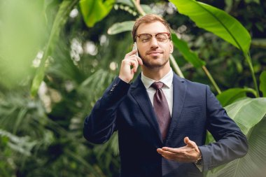 handsome businessman in suit, tie and glasses with closed eyes talking on smartphone and breathing fresh air in greenhouse