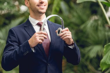 cropped view of smiling businessman in suit and tie holding wireless headphones in greenhouse