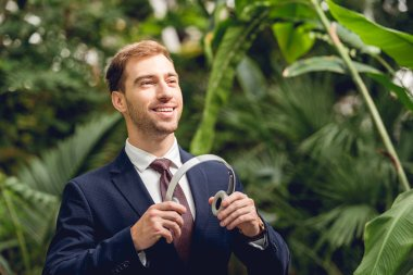 smiling businessman in suit and tie holding wireless headphones in greenhouse