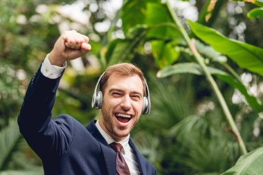 happy businessman in suit and wireless headphones showing yes gesture in greenhouse