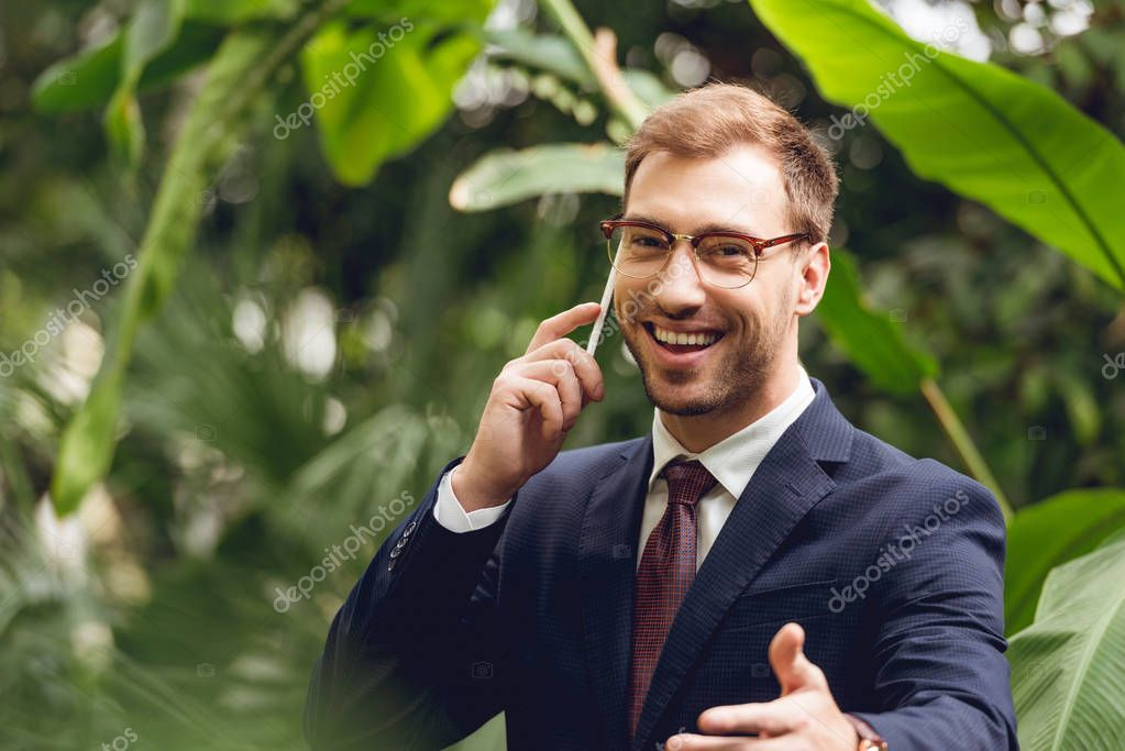 happy businessman in suit, tie and glasses talking on smartphone in greenhouse