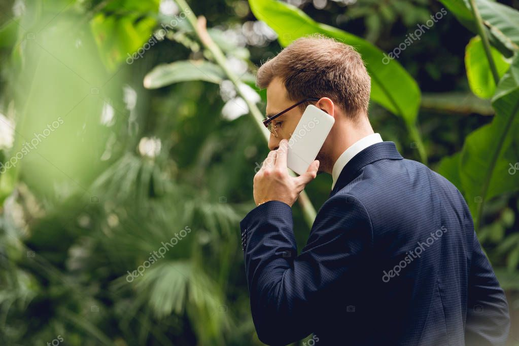 businessman in suit and glasses talking on smartphone in greenhouse