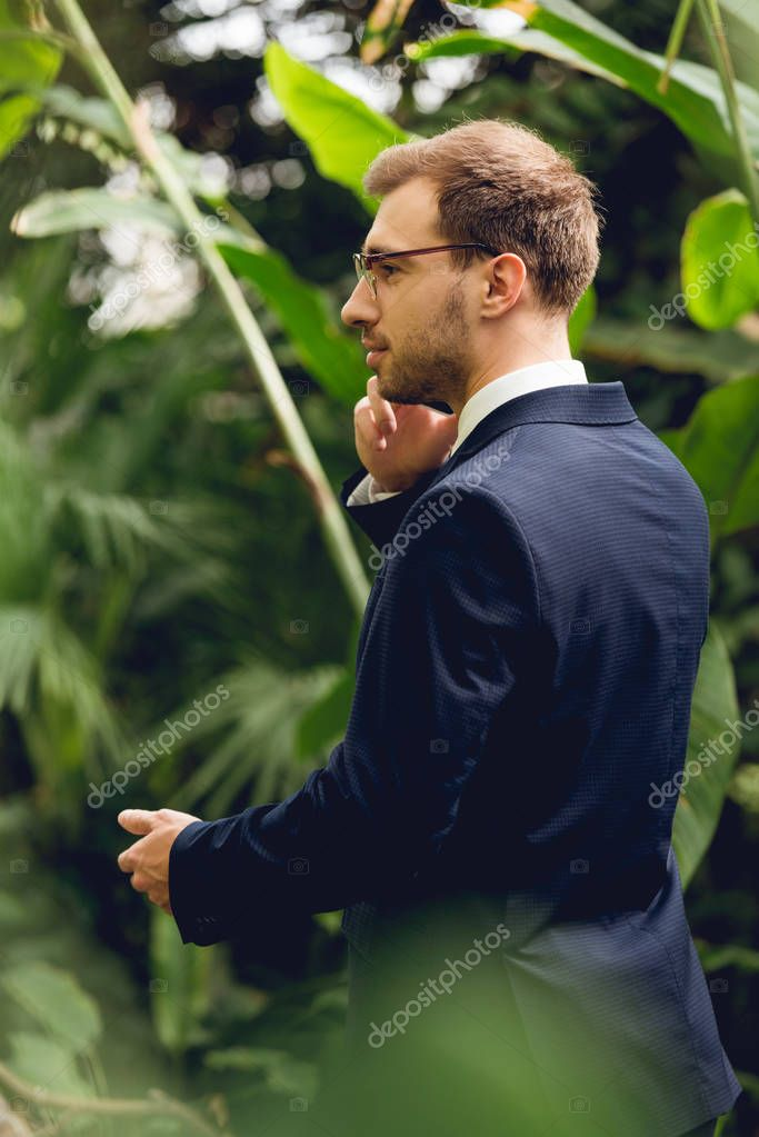 businessman in suit and glasses talking on smartphone in greenhouse and looking away