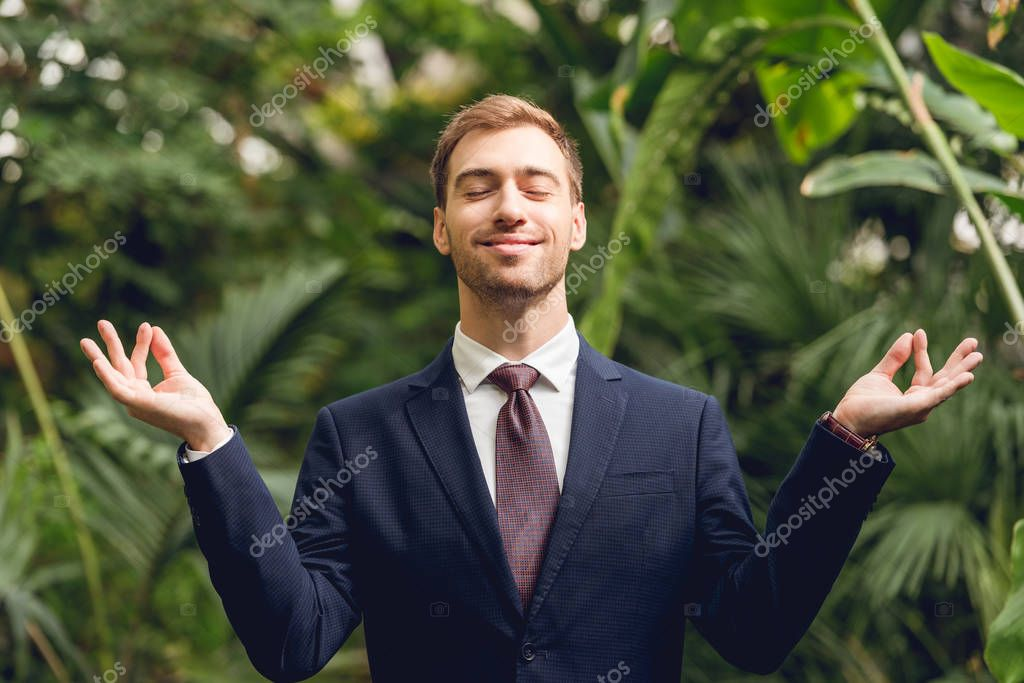 handsome smiling businessman in suit and tie with closed eyes meditating in orangery