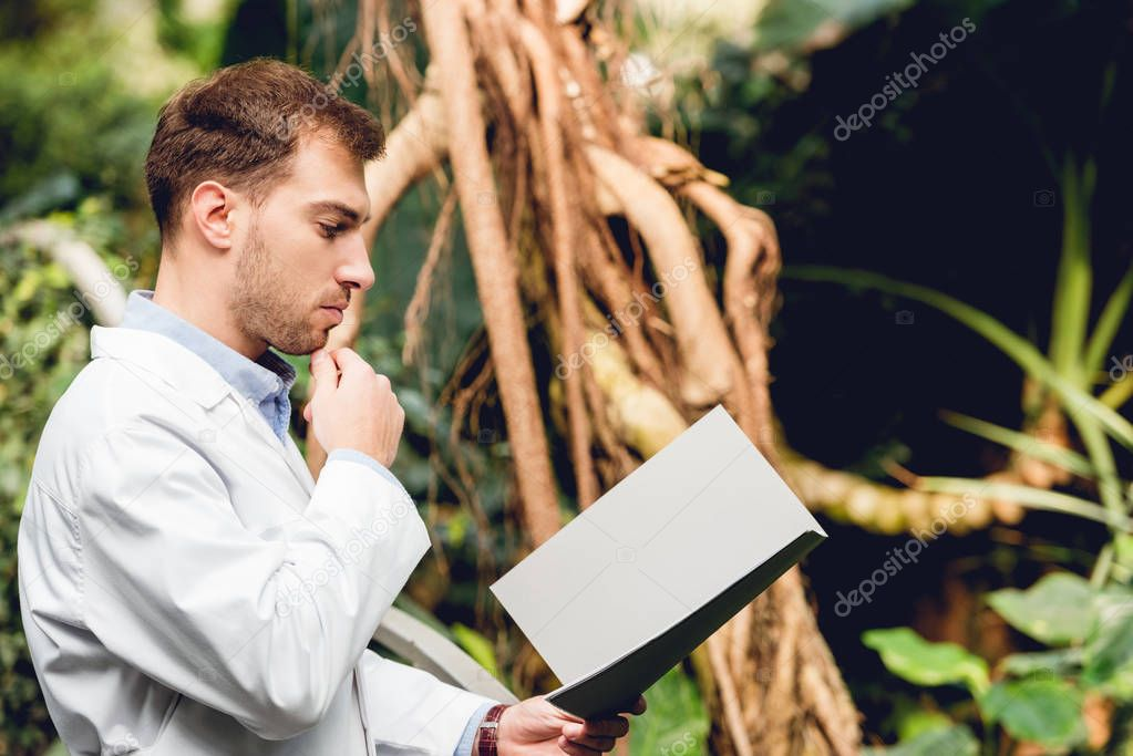 pensive scientist in white coat reading book in orangery