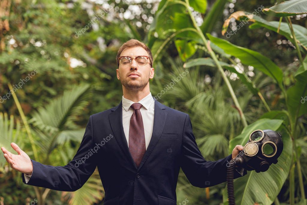 handsome businessman in suit and glasses with closed eyes holding rubber gas mask in orangery