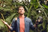 Lächelnder Reisender mit Rucksack und geschlossenen Augen atmet frische Luft, während er im tropischen Wald eine Gasmaske hält