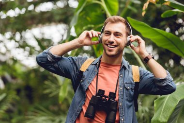 happy traveler with backpack and binoculars listening music in headphones in tropical forest
