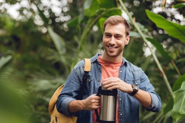 selective focus of smiling traveler with backpack opening thermos in tropical forest