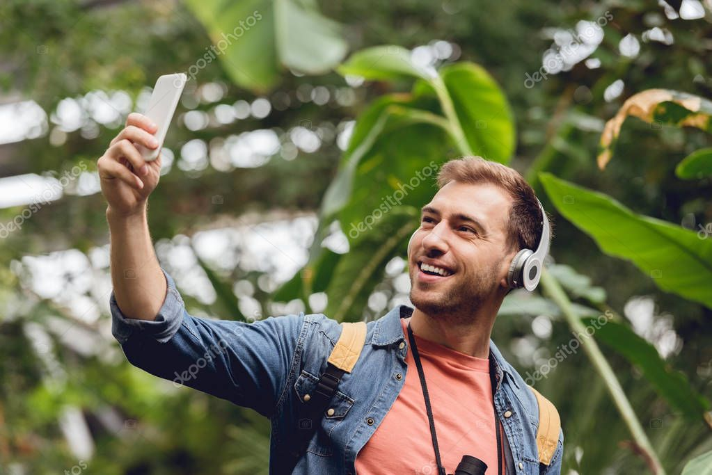 happy traveler in headphones taking selfie in green tropical forest