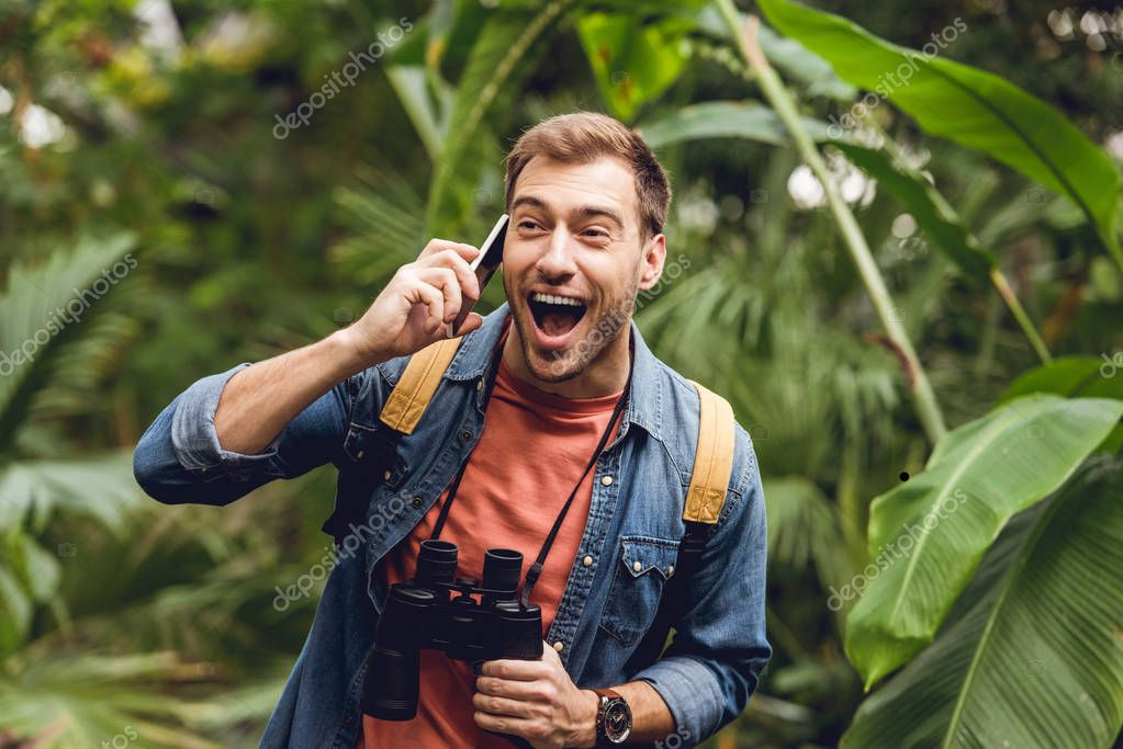 happy traveler with backpack and binoculars talking on smartphone in green tropical forest