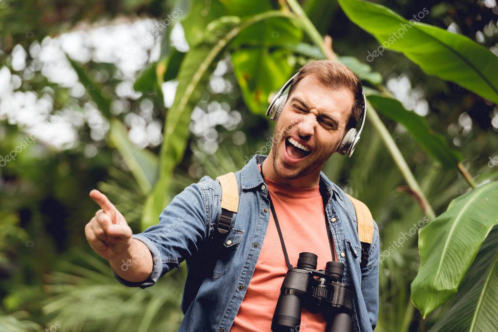 excited traveler with backpack and binoculars listening music in headphones and singing in tropical forest