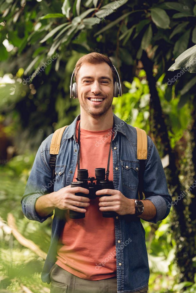 smiling traveler with backpack and binoculars listening music in headphones in green tropical forest