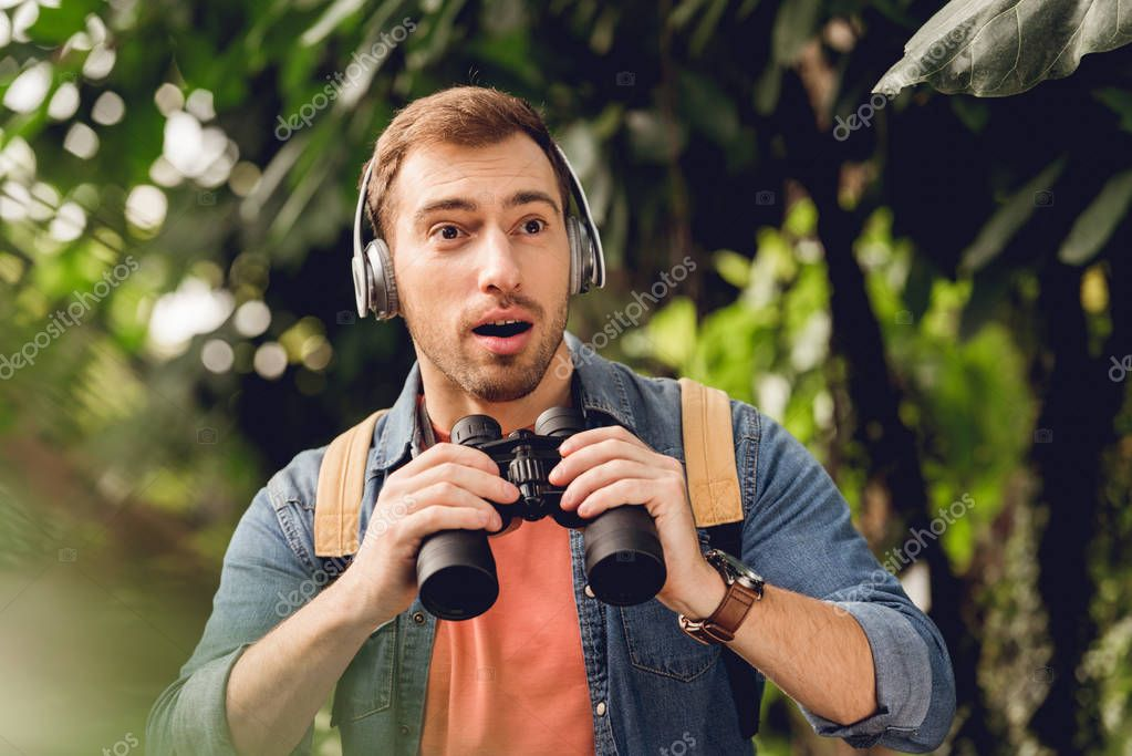 surprised traveler with backpack and binoculars listening music in headphones in green tropical forest