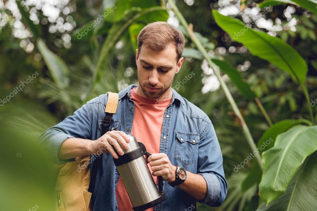 selective focus of traveler with backpack opening thermos in tropical forest