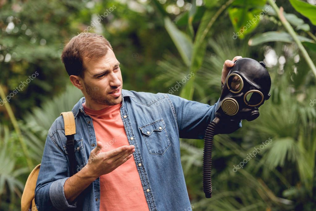 confused traveler with backpack pointing at gas mask in tropical forest