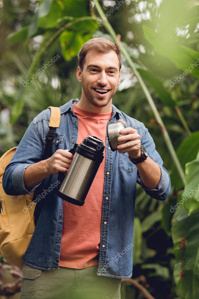 selective focus of happy traveler with backpack opening thermos in tropical forest