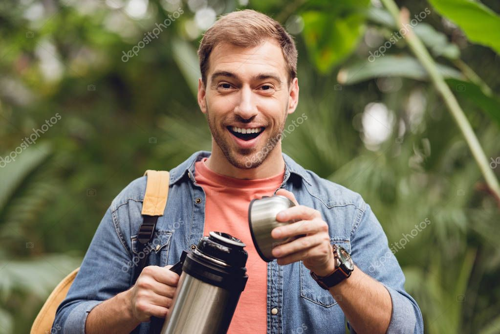 happy traveler with backpack opening thermos in tropical forest