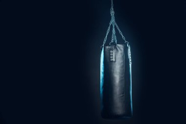 Leather punching bag hanging on steel chains on black