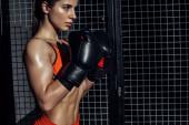 Fotografia Boxer sportivi in guanti da boxe in piedi vicino alla rete metallica e guardando lontano