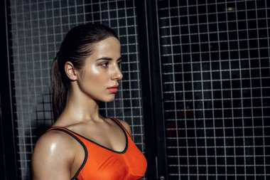Sportswoman standing near wire netting and looking away