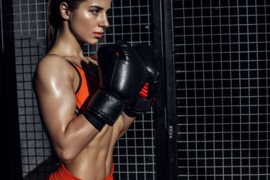 Sporty boxer in boxing gloves standing near wire netting and looking away