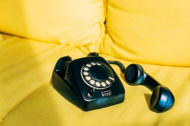 Sunshine on black retro phone on yellow sofa stock vector