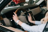 Fotografia cropped view of woman holding steering wheel while sitting in car