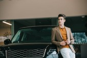 Fotografie handsome man standing near automobile in car showroom