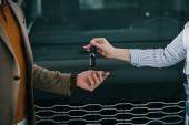 ostříhané zobrazení obchodníka s automobily, který dává klíč člověku v autosalónu