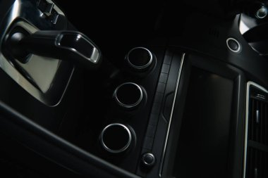 black buttons near modern car dashboard and gear shift in automobile