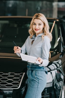 happy blonde car dealer holding clipboard and pen in car showroom