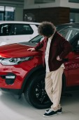 Fotografie kadeřník, který se dívá na červený automobil, zatímco stojí v autosalónu