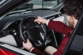 Fotografia selective focus of curly driver holding steering wheel while sitting in car